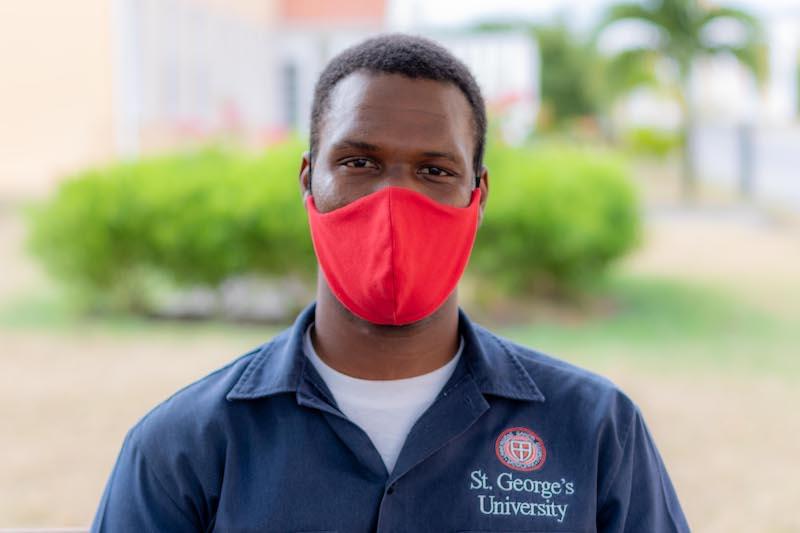 Man wearing protective mask in an SGU shirt smiling at camera