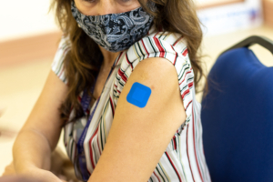 Woman in mask showing her arm with a blue bandaid where she received her vacciniation