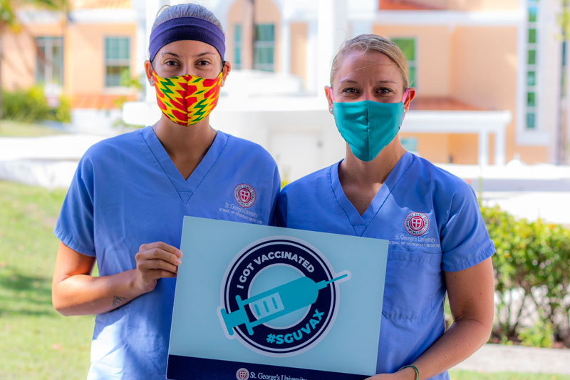Woman in a mask holding a sign that shows she got her COVID vaccine